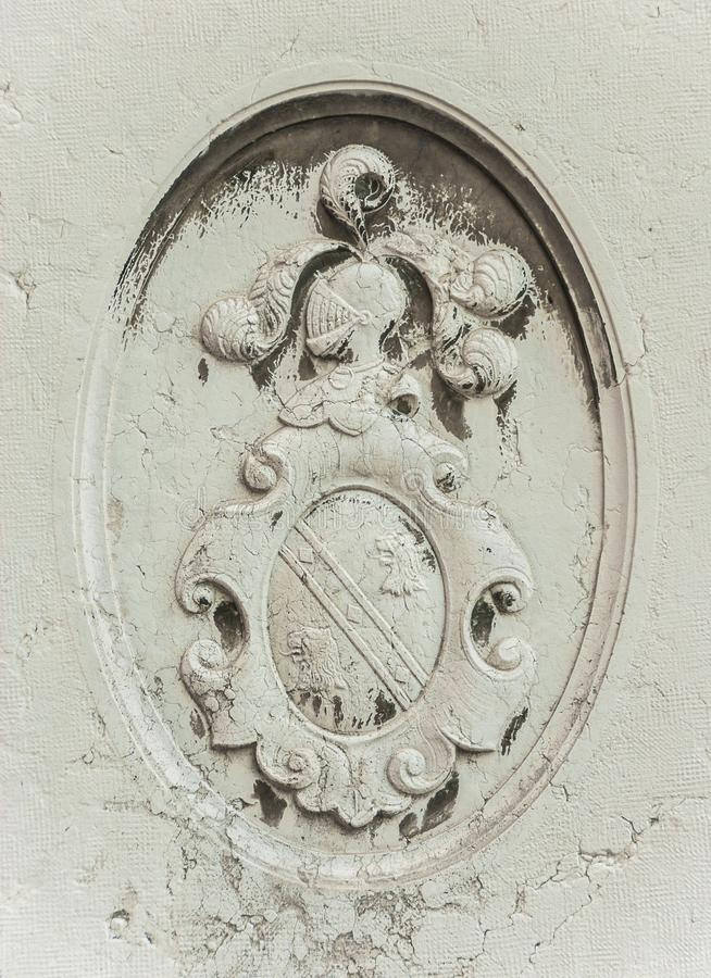 Heraldic emblem in Venice. Old heraldic emblem relief with helm and shield on a Venice wall stock image