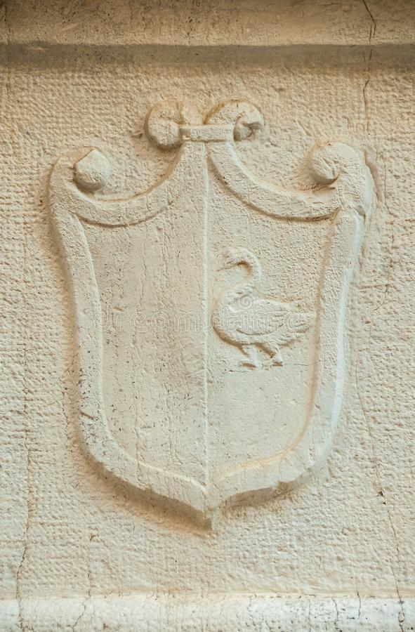 Heraldic emblem with swan in Venice. Old heraldic emblem with a swan relief on a Venice wall stock photography