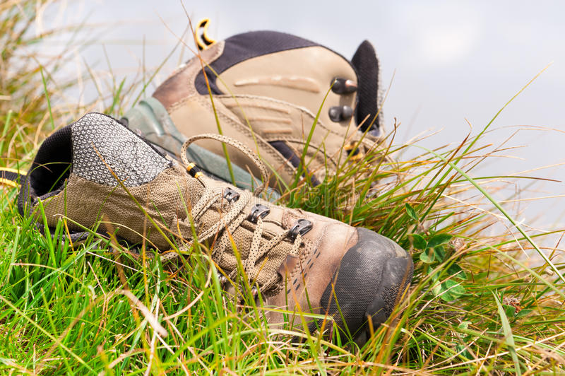 Old hiking boots close-up. On green grass stock photography