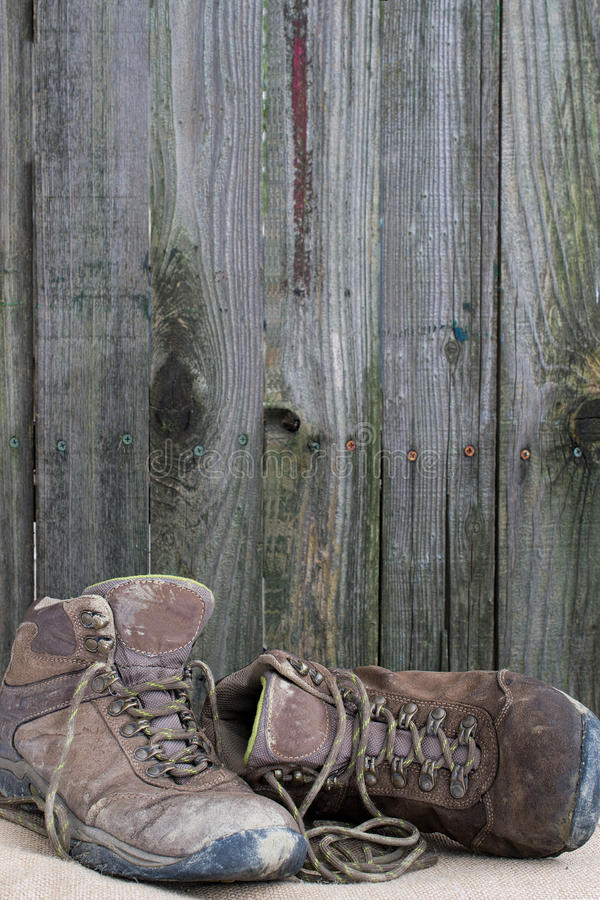 Old hiking shoes. Pair of old hiking boots on matt, against wooden fence background, illustrating the concepts of worn out, used, resting, or hiking in nature stock image