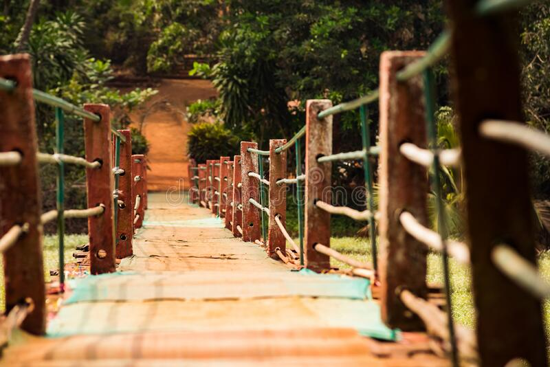 Old hinged pedestrian bridge over swamp to spice plantation in GOA / India stock image
