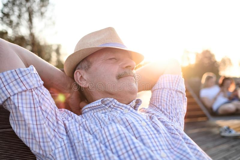 Old hispanic man sits on bench, smiling, enjoying summer sunny day. All problems left behind. Concept of happy retired person royalty free stock photos