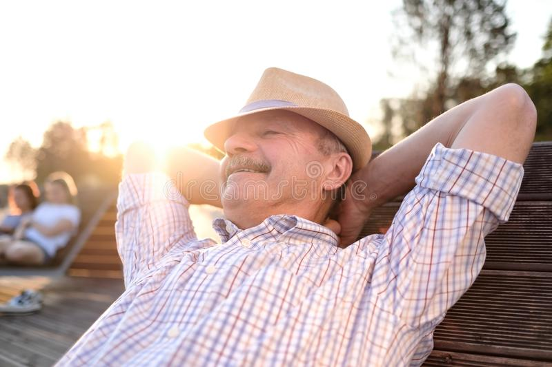 Old hispanic man sits on bench, smiling, enjoying summer sunny day. All problems left behind. Concept of happy retired person royalty free stock image