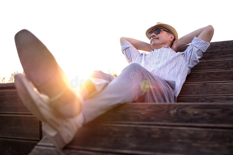Old hispanic man sits on bench, smiling, enjoying summer sunny day. All problems left behind. Concept of happy retired person Full length royalty free stock photos