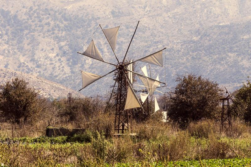 Old windmills Lassithi area, island Crete, Greece. Old, historic, famous, metallic windmills who pump water out of the ground for irrigation of fields on a sunny royalty free stock image