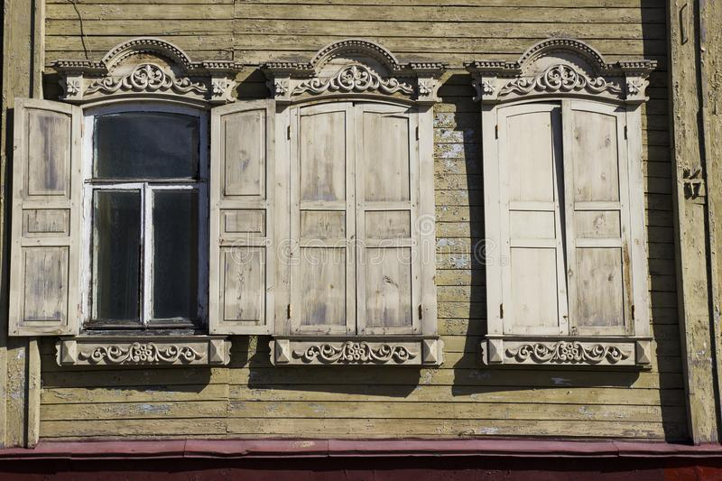 Old historic house. Russian architecture. Windows of old log house with carved wooden trim. Carved wooden trim facade. stock photography