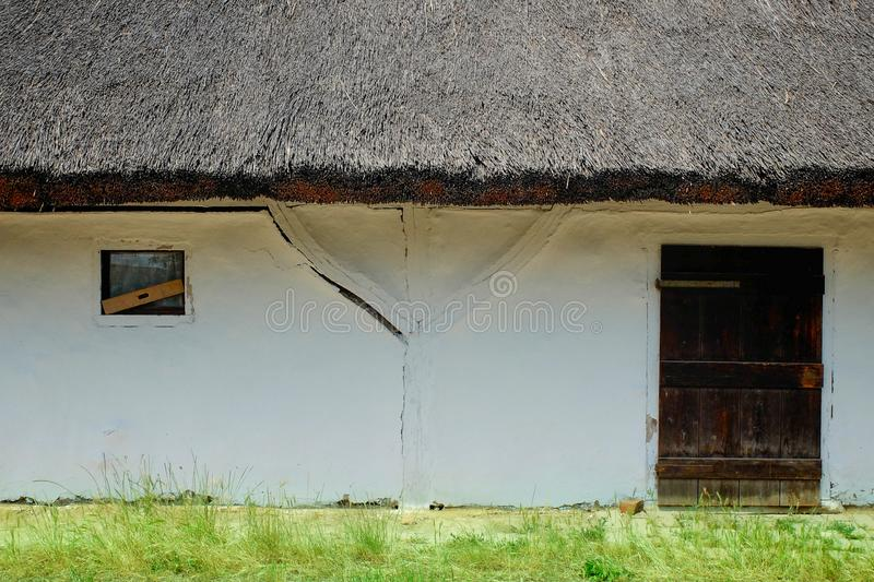 Old historic rural farm house with thatch roof. Doors and windows visible stock photos