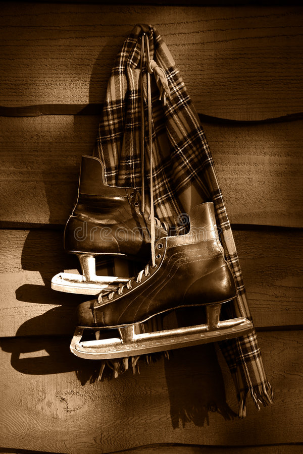 Old hockey skates. With scarf hanging on a wall/ Sepia tone royalty free stock image