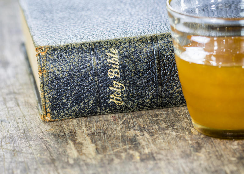 The old holy bible with a cup of honey. On wooden background, conceptual image stock image