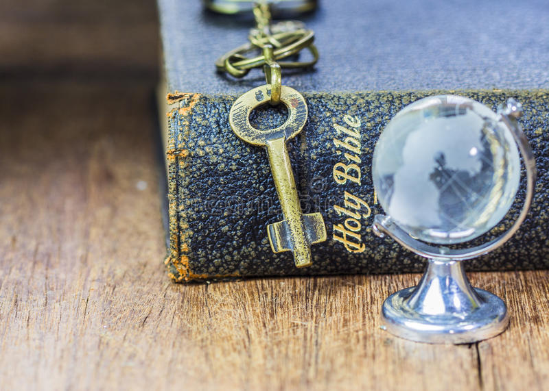 The old holy bible with metal key and globe icon on wooden background royalty free stock image