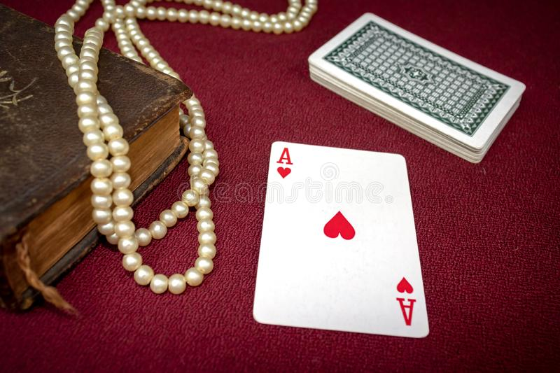 Old holy bible, rosary beads, ace of hearts and stack of cards on wooden table. Misticism and fortune telling, future prediction c. Oncept stock photos