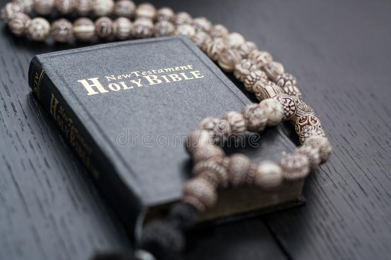 Old holy bible and rosary beads on rustic table. Old holy bible and rosary beads on rustic wooden table stock images