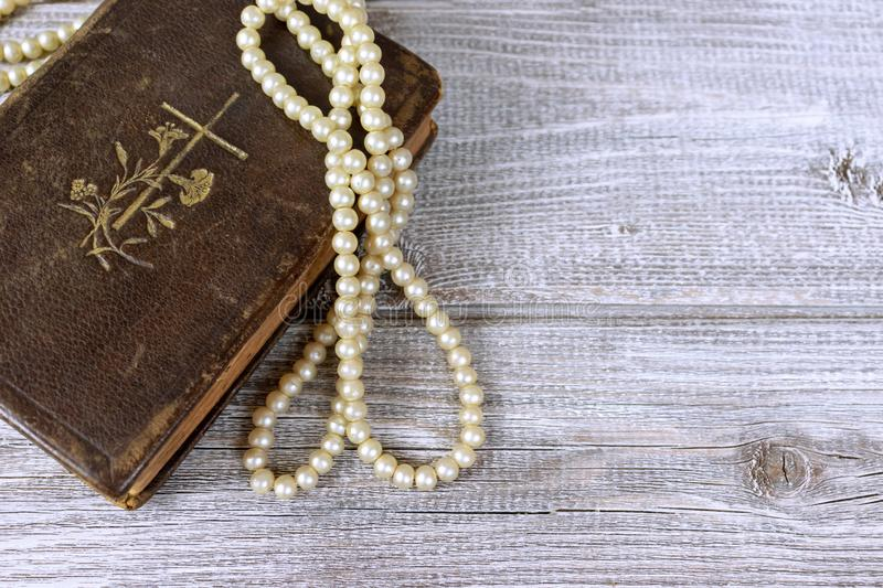 Old holy bible and rosary beads on rustic wooden table.  stock images