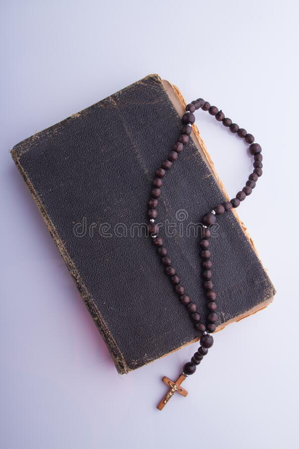 Old holy bible and rosary necklace. White isolated background stock photos