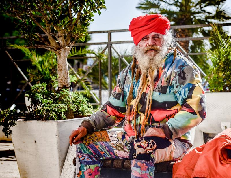Old homeless guru roaming around. The old town of Taranto hoping to find something to eat and drink royalty free stock image