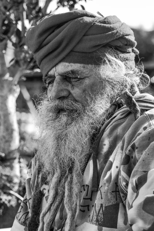 Old homeless guru roaming around. The old town of Taranto hoping to find something to eat and drink stock photography