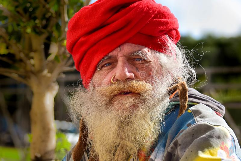 Old homeless guru roaming around. The old town of Taranto hoping to find something to eat and drink stock photos