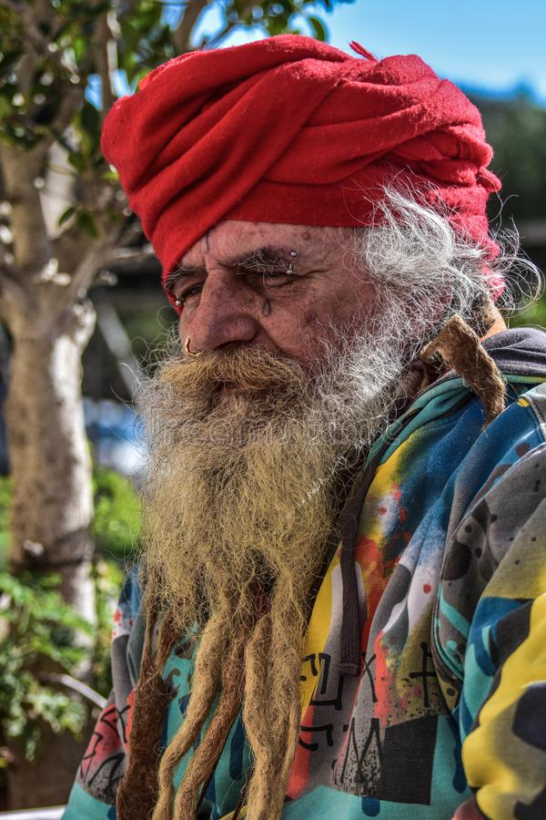 Old homeless guru roaming around. The old town of Taranto hoping to find something to eat and drink royalty free stock photo