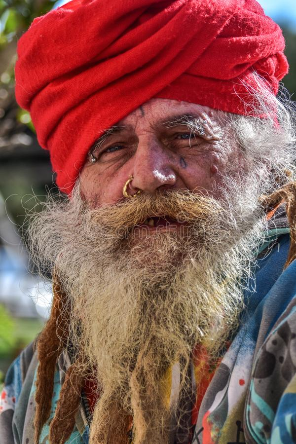Old homeless guru roaming around. The old town of Taranto hoping to find something to eat and drink royalty free stock photography