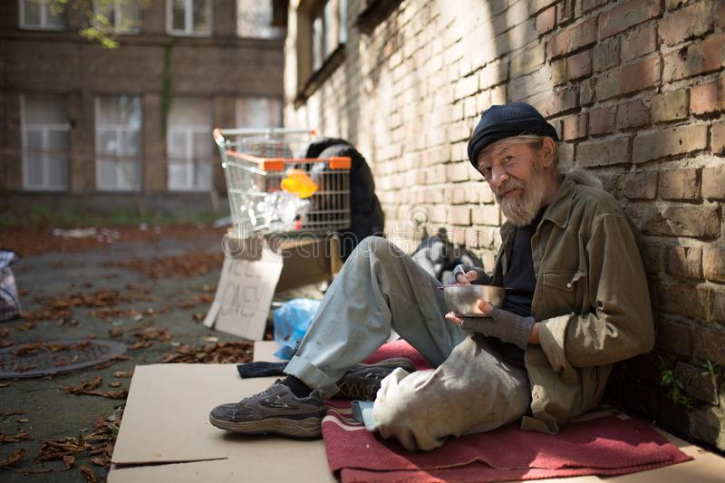 Old homeless man sitting on cardboard holding bowl with food in hand. stock images