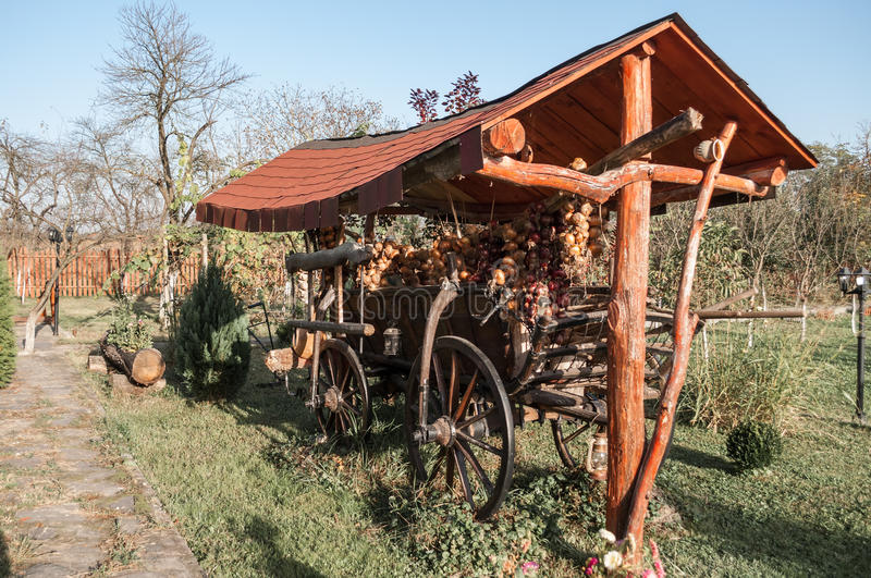 Old horse cart decorated with onion ropes in a garden. An old horse cart decorated with onion ropes in a garden royalty free stock photography