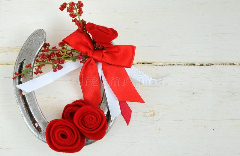 An old horseshoe decorated with red roses made of felt with red and white ribbons on a white washed rustic wooden background. royalty free stock images