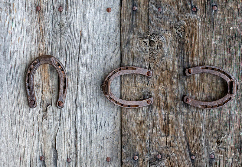 Old horseshoes on wooden background royalty free stock photo