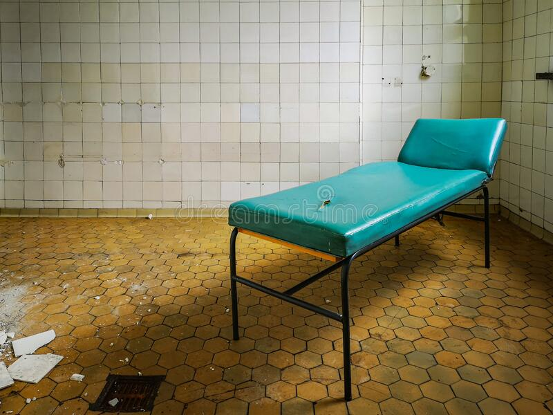 Old hospital bed standing in empty room in old hospital. Old hospital bed standing in empty room in old abandoned hospital royalty free stock photos