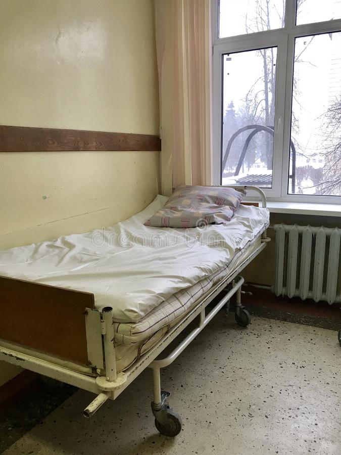 The old hospital from the inside. Filled bed for the nurse on duty in the corridor. stock photography
