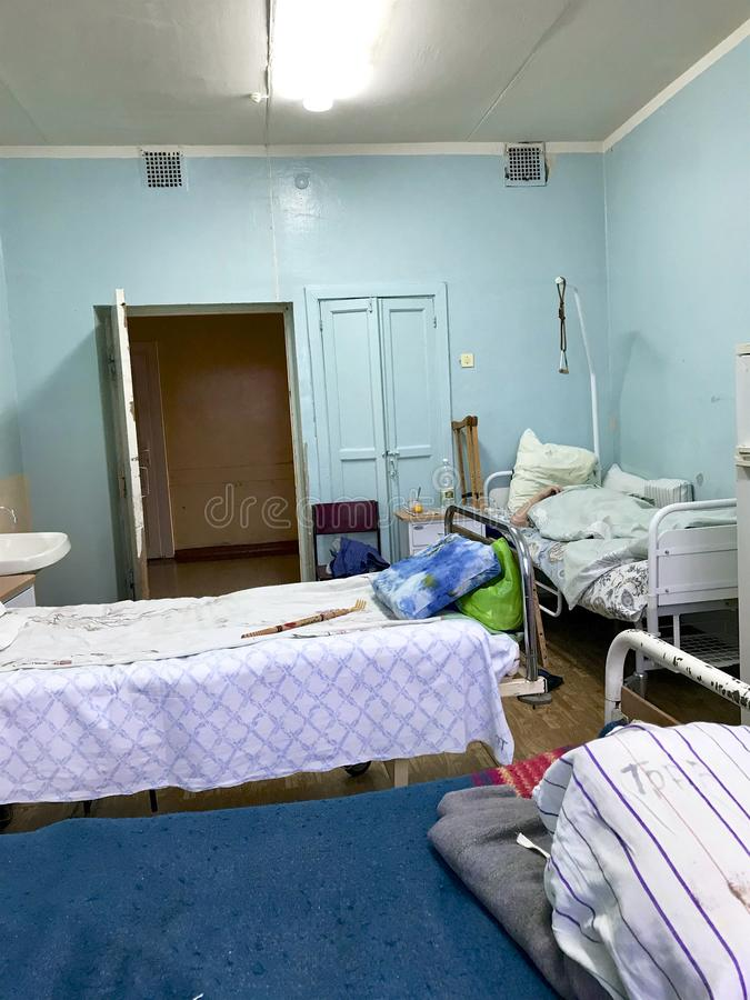 The old hospital from the inside. Filled beds of patients and their personal belongings left on the beds and nightstands. One of t stock image
