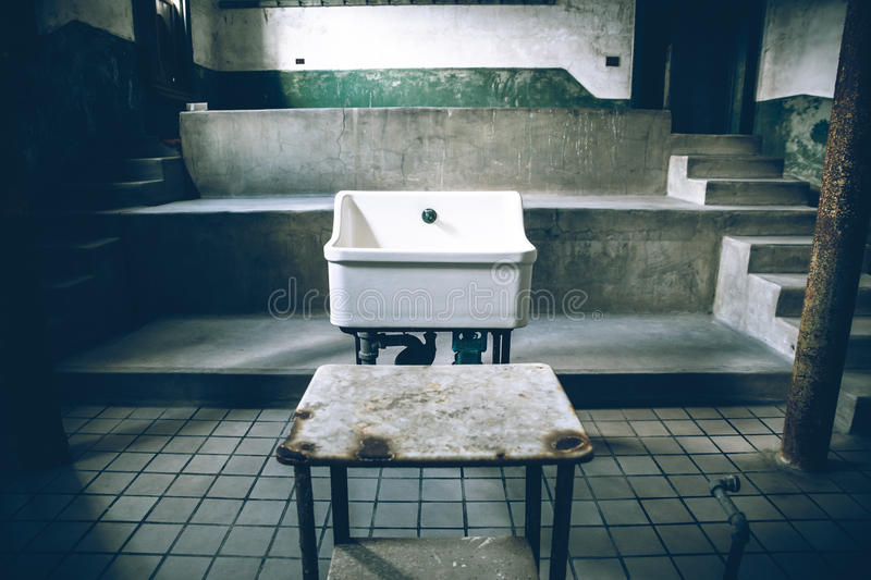 Old Hospital Sink. NEW YORK CITY - OCTOBER 19, 2015: View of sink in old surgery room at abandoned Ellis Island Hospital stock image