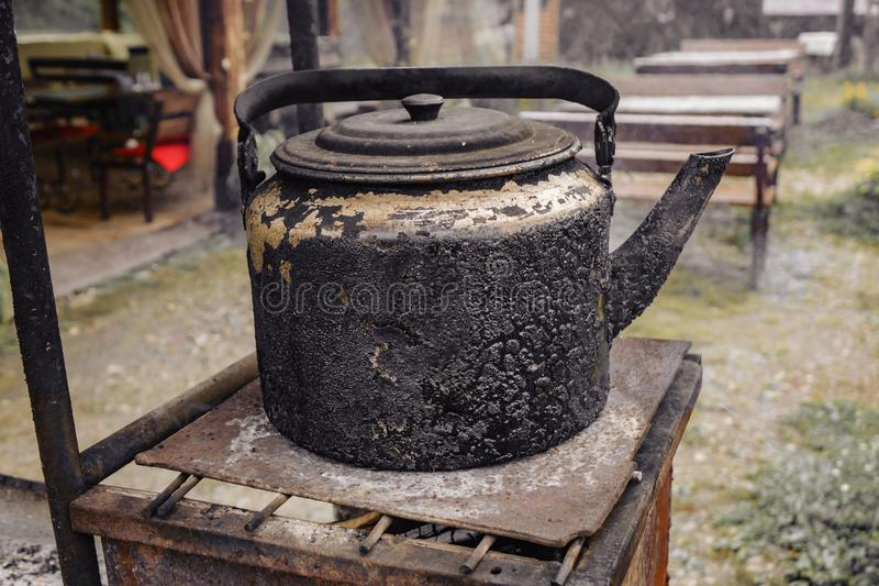Old hot kettle on a charcoal stove used for a long time in the kitchen. Background, water, retro, food, vintage, texture, coffee, nature, antique, black, boil royalty free stock images