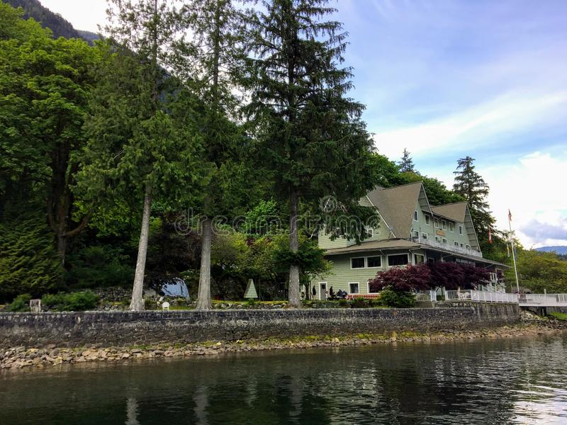 An old hotel beside the ocean surrounded by tall evergreen trees in British Columbia, Canada royalty free stock photos