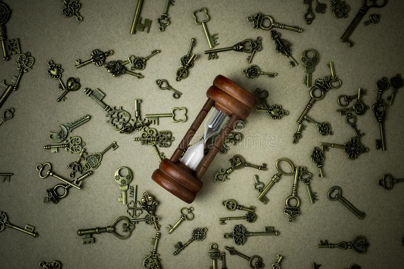 Old hourglass and classic keys on brown paper. stock photography