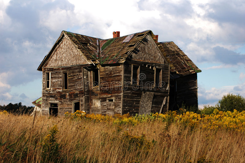 Old House. An old abandoned house against a cloudy blue sky stock photo