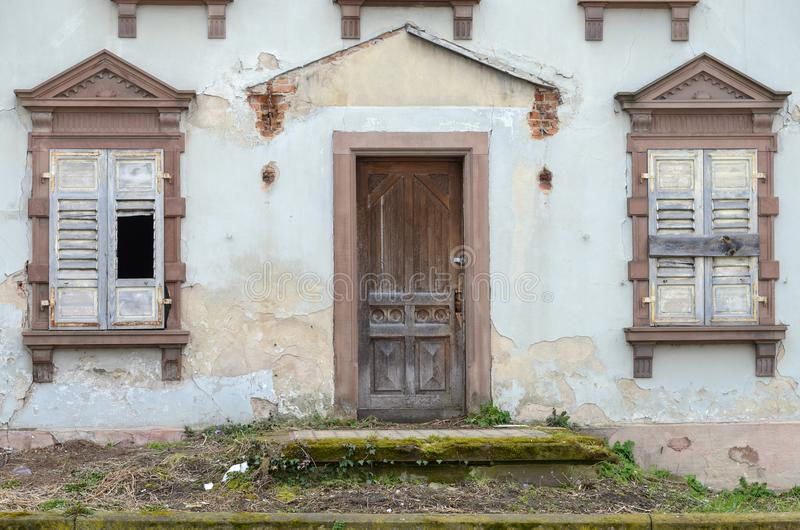 Old house with broken and boarded up shutters royalty free stock image
