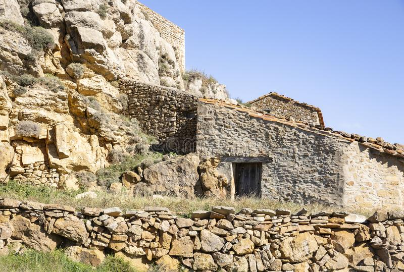 Old house built against the castle wall in Puertomingalvo stock images