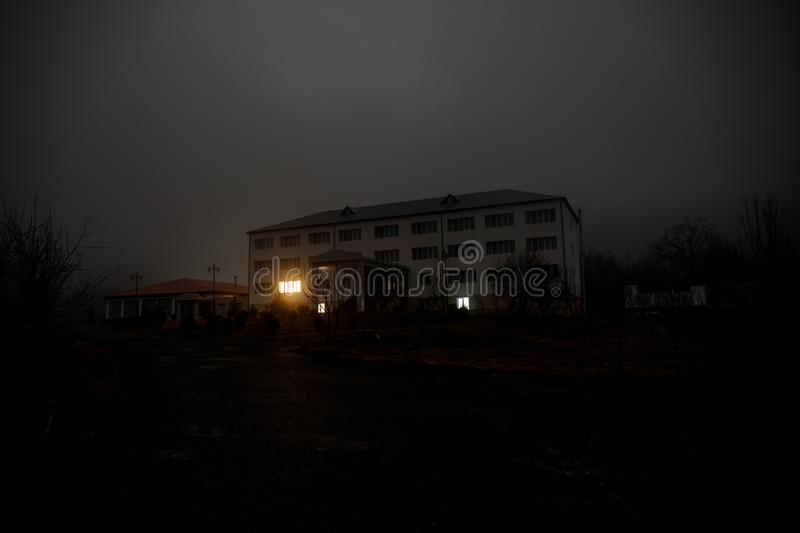 Old house with a Ghost in the forest at night or Abandoned Haunted Horror House in fog. Old mystic building in dead tree forest. C royalty free stock photo