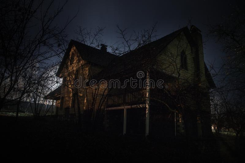 Old house with a Ghost in the forest at night or Abandoned Haunted Horror House in fog. Old mystic building in dead tree forest. royalty free stock image