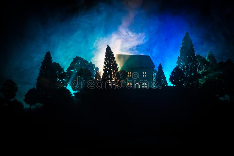Old house with a Ghost in the forest at night or Abandoned Haunted Horror House in fog. Old mystic building in dead tree forest. stock photos