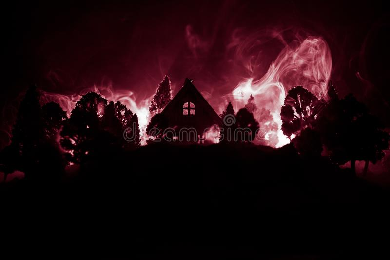 Old house with a Ghost in the forest at night or Abandoned Haunted Horror House in fog. Old mystic building in dead tree forest. stock photo