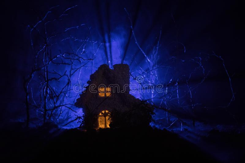 Old house with a Ghost in the forest at night or Abandoned Haunted Horror House in fog. Old mystic building in dead tree forest. royalty free stock photos