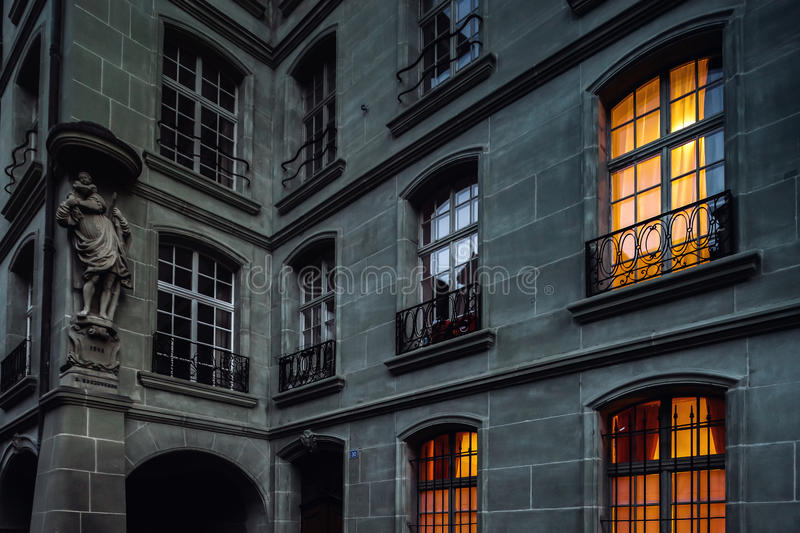 Old house with highlighted yellow windows, night view stock photography