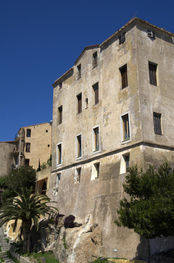 Old house in historical city Calvi on island Corsica,France. Old house and steps with blue sky and palm tree in Calvi on island Corsica,France royalty free stock photography