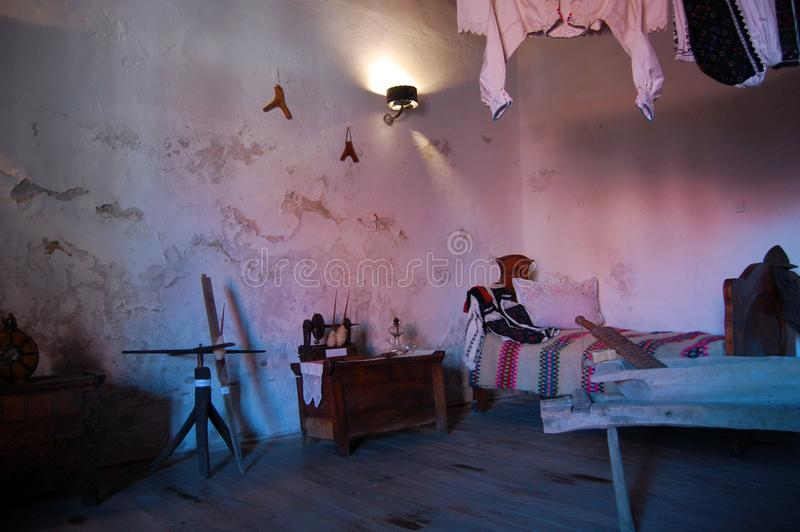 Old house interior view, vintage clothes, bed and household objects. In home interior royalty free stock photography