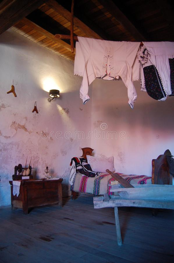 Old house interior view, vintage clothes, bed and household objects. In home interior royalty free stock images