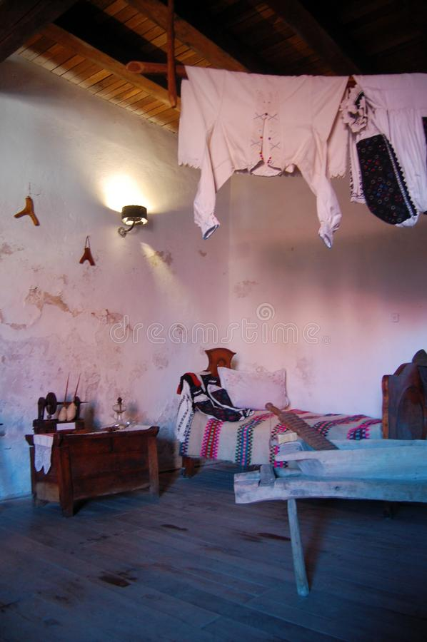Old house interior view, vintage clothes, bed and household objects. In home interior stock photography
