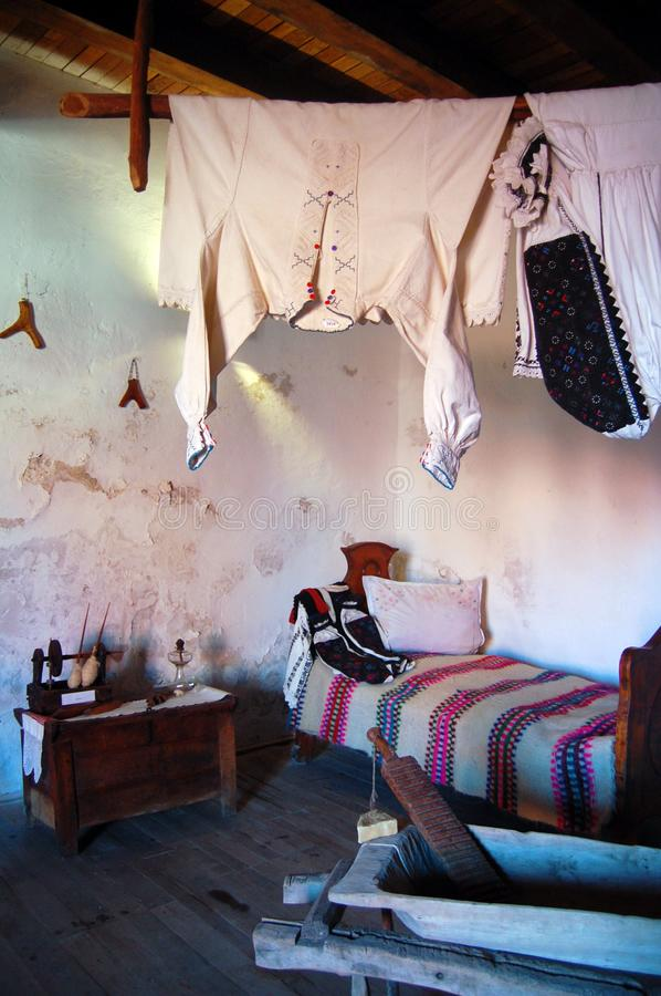 Old house interior view, vintage clothes, bed and household objects. In home interior stock photo