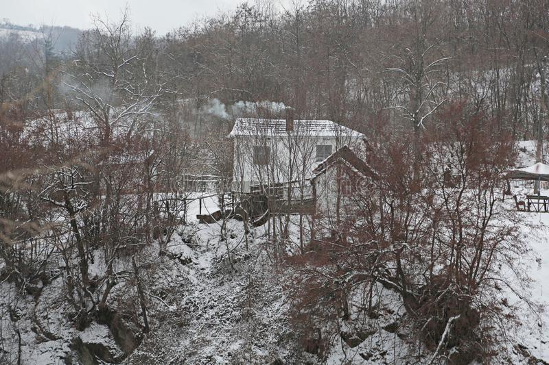 Old house lodge in the forest in mountains. From a pipe there is a smoke. Winter landscape. royalty free stock photography