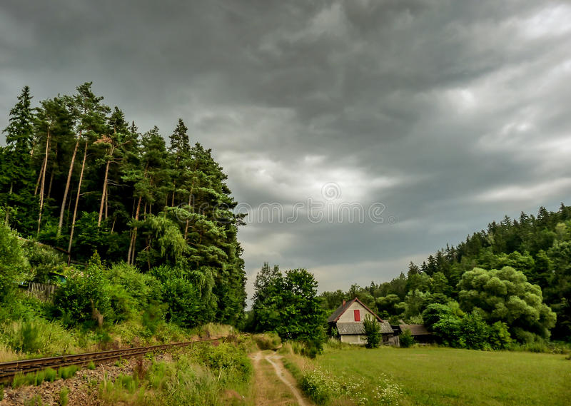 Old house near the forest beside the road and track. stock photos
